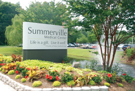 Summerville Medical Center's entrance sign by fountain and flowerbed.
