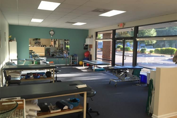 Inside Grace Physical Therapy & Sports Rehab showing adjustment tables, equipment, front desk and the storefront