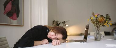 A young woman has fallen asleep at her computer while studying at the dining room table